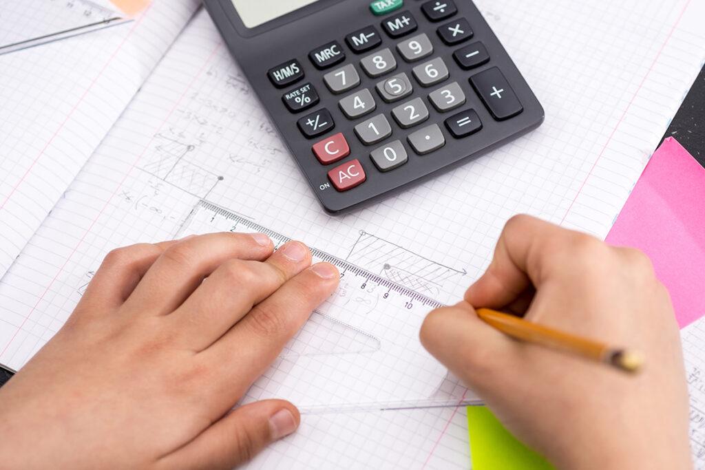 Barnehender med kalkulator og linjal