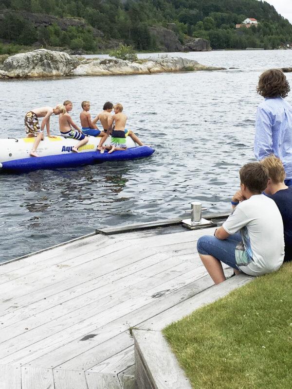Barn på sommerleir morer seg på og ved vannet