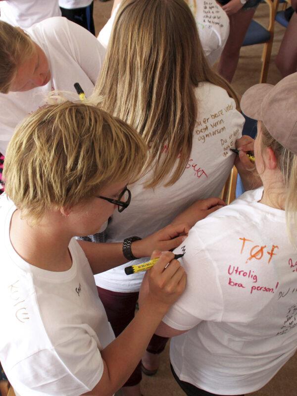 Ungdommer skriver på hverandres t-skjorter
