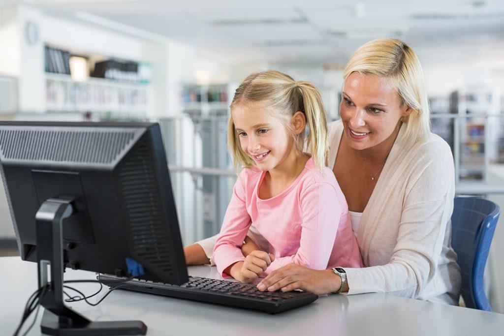 Jente og lærer foran pc