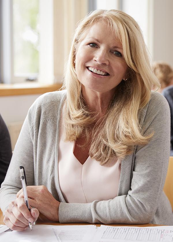 Kvinne sitter med pennen klar på kurs