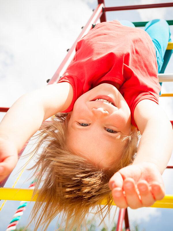 Jente henger opp ned i klatrestativ