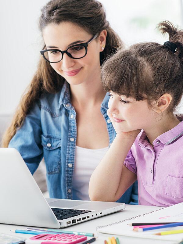 Mor og datter sitter ved PC-en