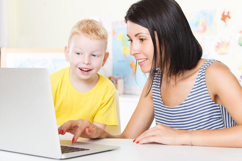 Skolegutt og lærer ved pc-en