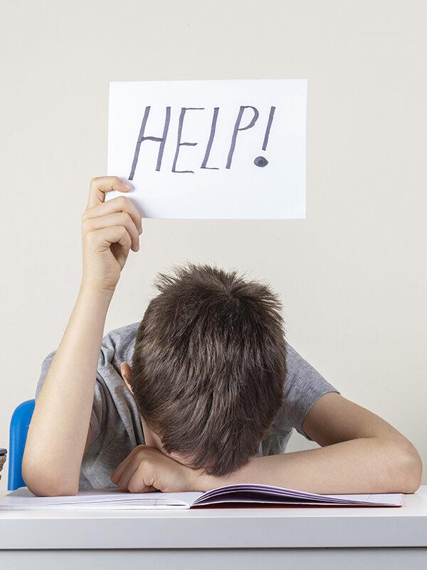 """Gutt ligger bøyd over bok og holder opp et skilt der det står """"help"""""""