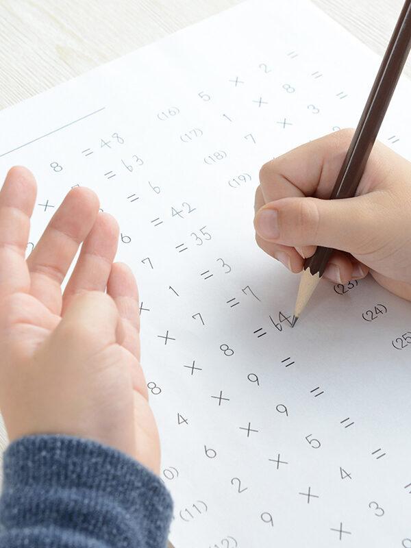 Barnehender gjør regnestykker på et ark