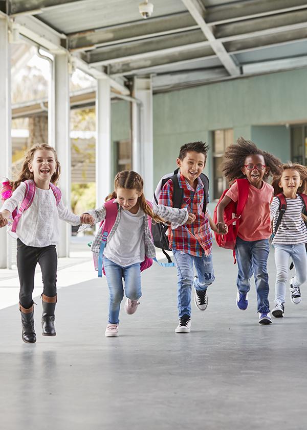 Skolebarn løper mens de holder hverandre i hendene