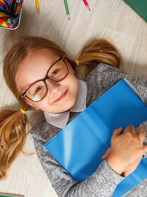 Jente med briller ligger på gulvet med en bok
