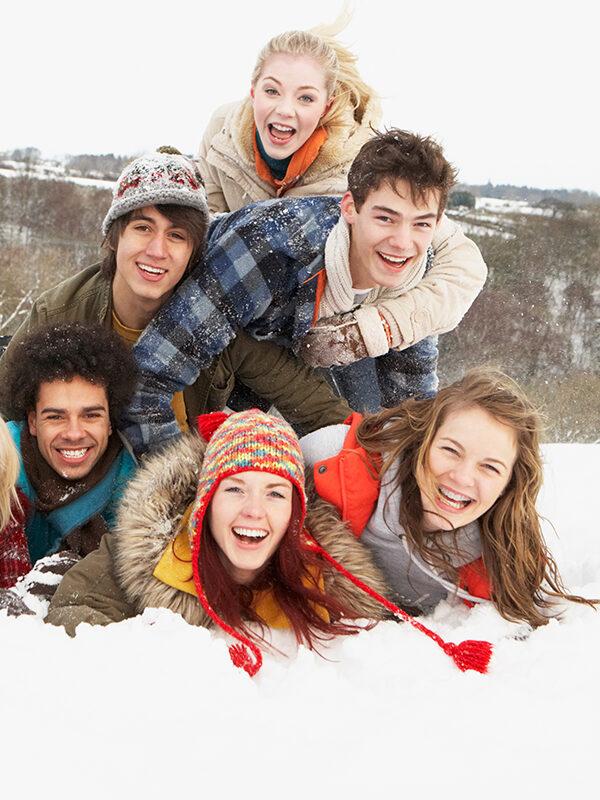 Ungdommer ligger oppå hverandre i snøen