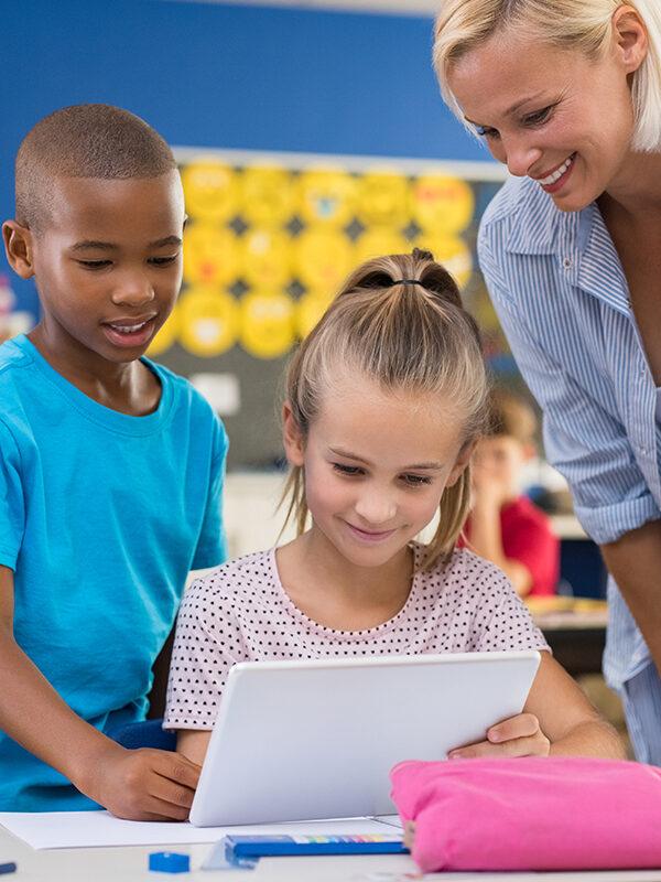 To elever og en lærer ser på et nettbrett