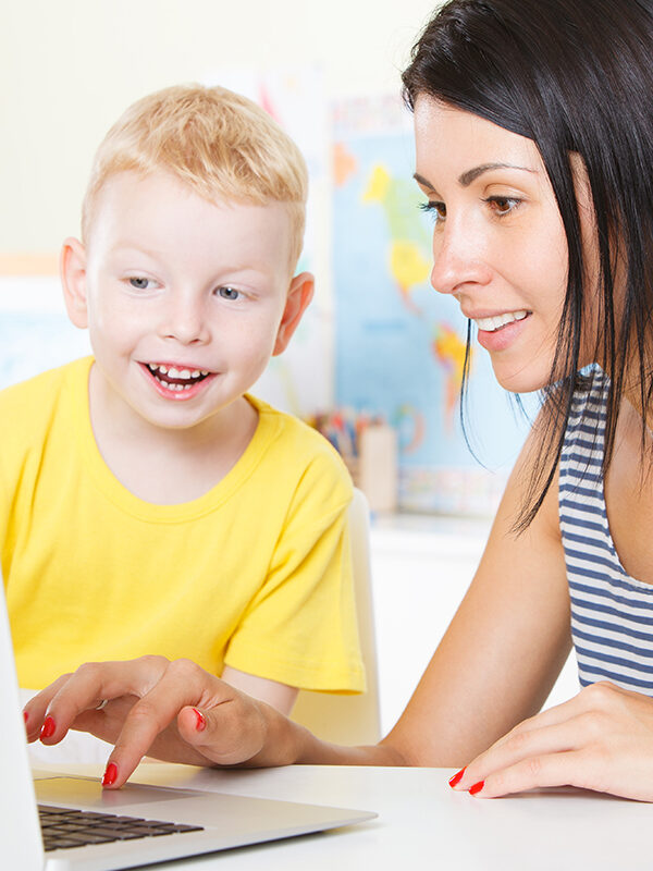 Lærer hjelper gutt ved pc-en