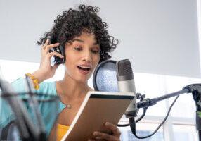 Kvinne leser fra manus mens hun lager podkast